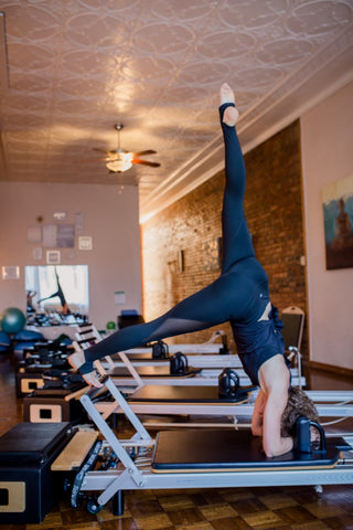 Woman in downward dog on pilate machine