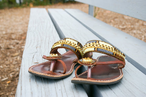 A pair of women's beaded leather sandals on a light blue bencg