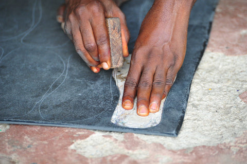 A pair of hands tracing a shoe print on a piece of rubber for a pair of sandals