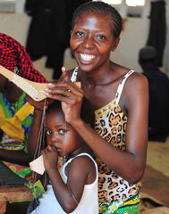 A mother holding a child and smiling while beading