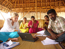 Several indian persons as well as a foreign woman sitting around a laptop in a large hut