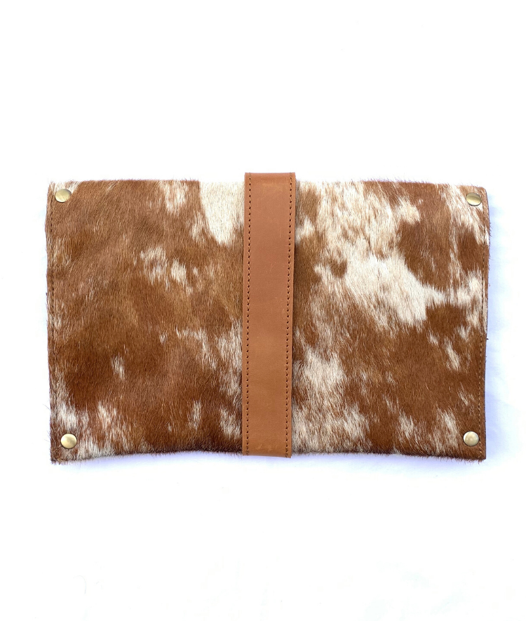 Meaningful cowhide clutch with tan and white hide and tan finished leather accents