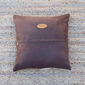 the brown faux suede back of an accent pillow with a RoHo logo in tan leather attached