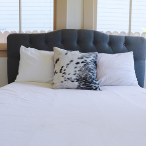 A handmade cowhide pillow in white and black spots decorating a bed