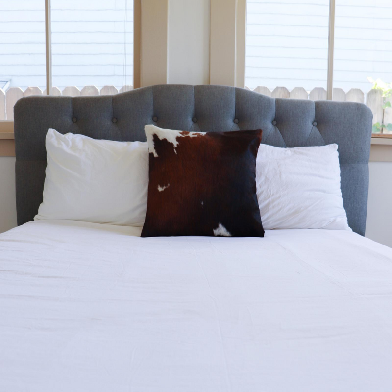 A brown and white cowhide accent pillow decorating a bed