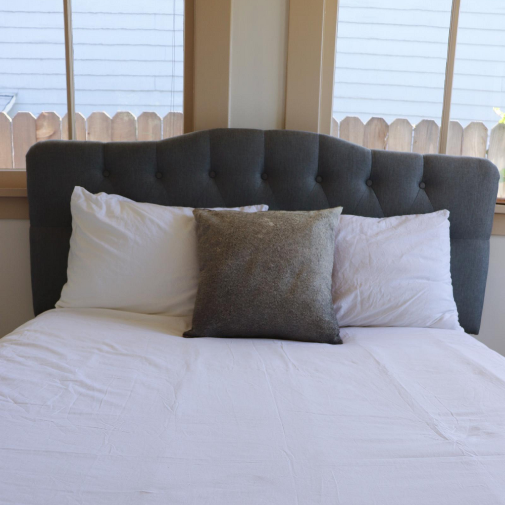 A grey cowhide accent pillow displayed on a bed
