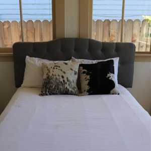 Two Kenyan cowhide pillows displayed on a bed