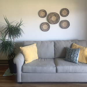 Five Fair Trade Binga Baskets displayed on a wall above a couch and house plant