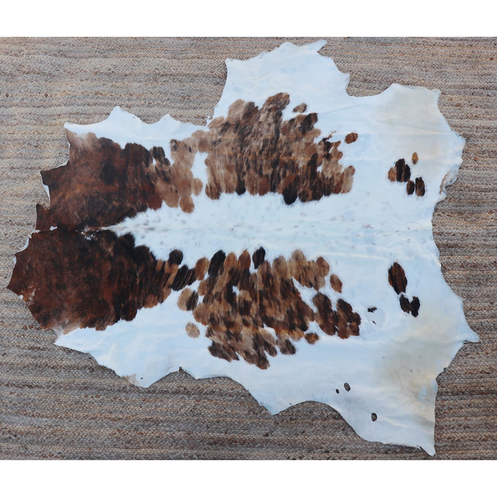 A light brown and white cowhide rug that comes from Kenya