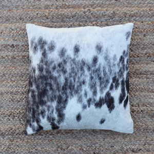 A Kenyan cowhide accent pillow in black spots and white