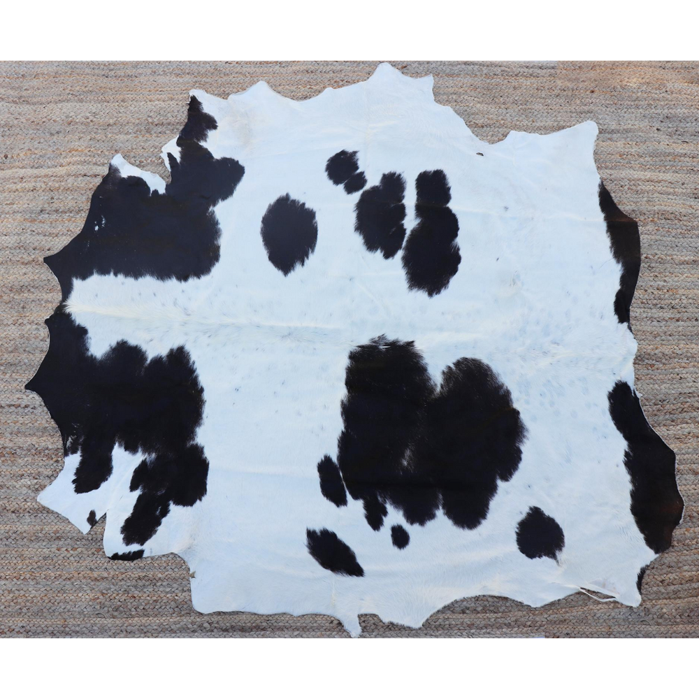 A large black and white cowhide rug from Kenya displayed on the top of a large sisal rug