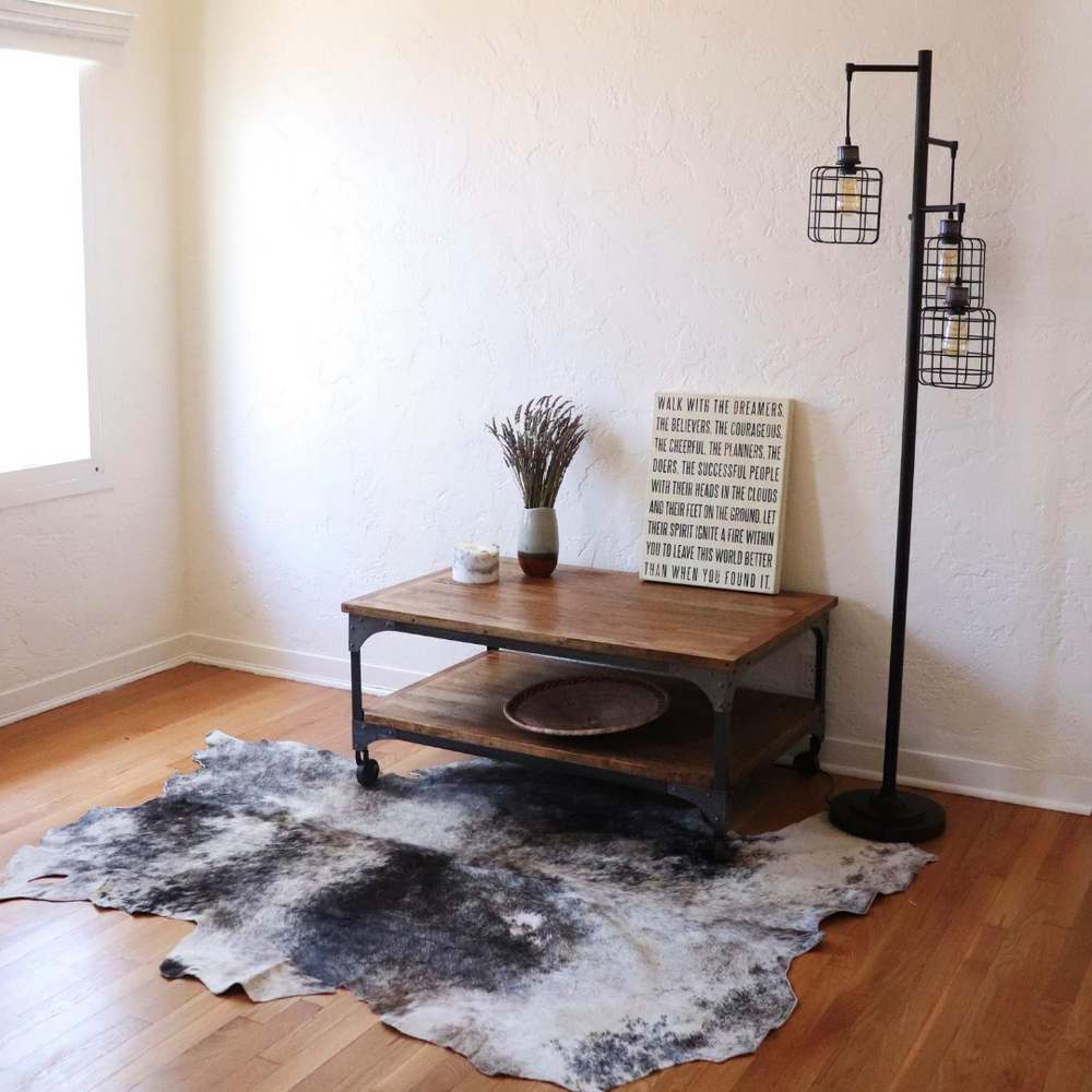 A Kenyan cowhide rug in grey being displayed under a coffee table and lamp