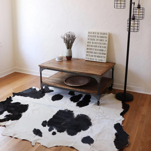 A Kenyan cowhide rug in black and white is displayed under a coffee table