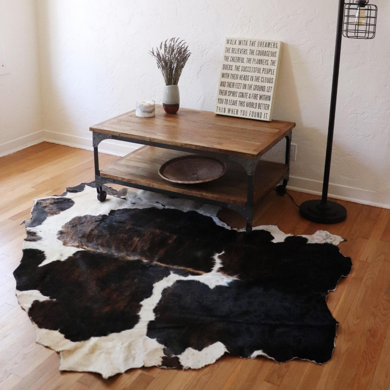 A dark brown and white rug displayed in a living room under a coffee table