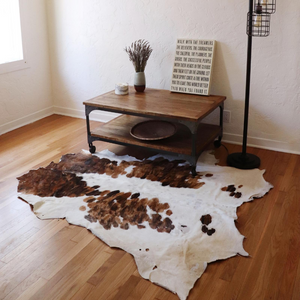 A Kenyan light brown and white cowhide rug that is displayed in a living room