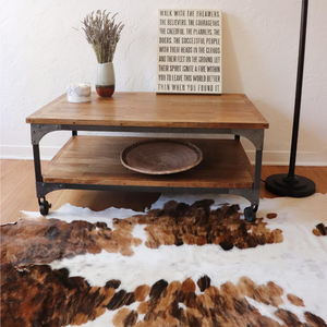 An image showing a coffee table with a vase and binga basket on it with a light brown and white cowhide rug underneath it