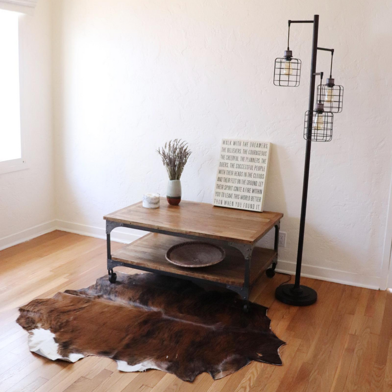 A black, brown and white cowhide rug displayed in a room