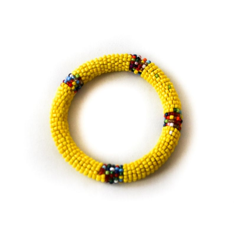 One single yellow beaded bangle bracelet against a white background
