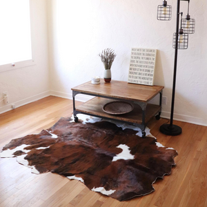 A tan, black and brown cowhide rug displayed partially under a coffee table