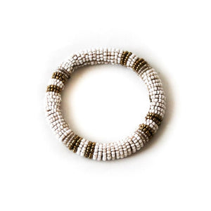 A single handmade white beaded bangle bracelet with gold accents on a white background