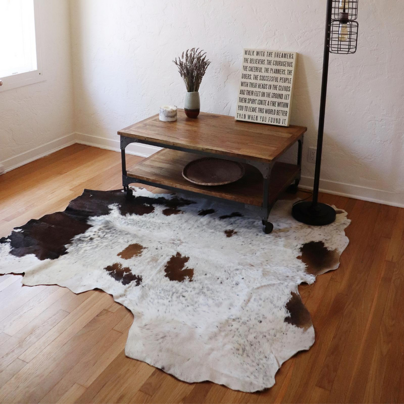 A Kenyan brown and white cowhide rug in a room with a coffee table and lamp