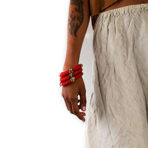 Three handmade red beaded small bangles on a model