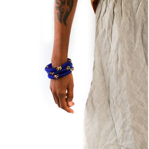 Three handmade blue beaded small bangles on a model