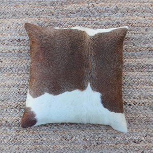 A brown and white cowhide accent pillow handmade by artisans in Kenya