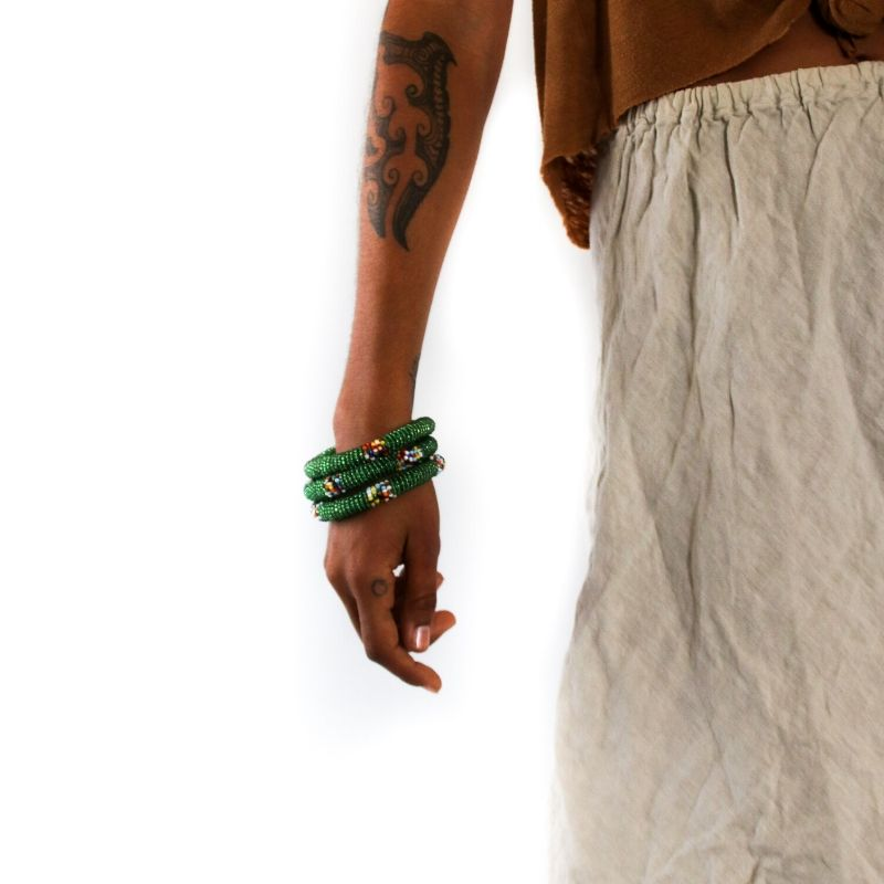 Three ethical green beaded small bangles on a model