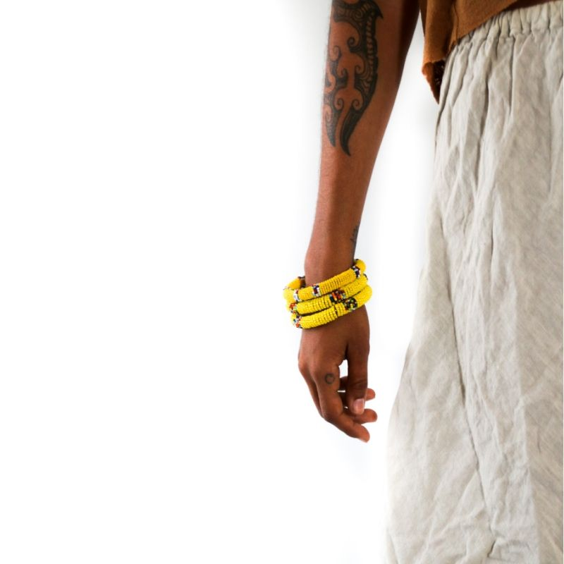 Three handmade yellow beaded small bangles with multicolored accents on a model