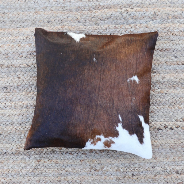 A dark brown and white cowhide accent pillow from Kenya
