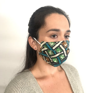 An earth toned African fabric face mask with a cause on a model with elastic over the ears