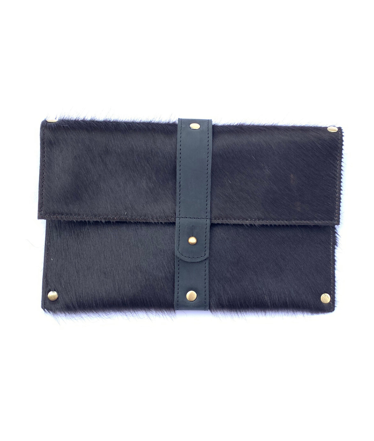 Purposeful cowhide clutch in all black hair with black finished leather accents on a white background