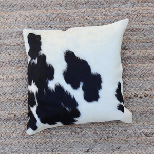 A Black and white cowhide pillow handmade by artisans in Kenya