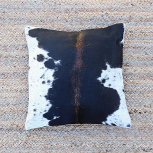 A Black and white cowhide pillow handmade by artisans in Kenya against a braided sisal background