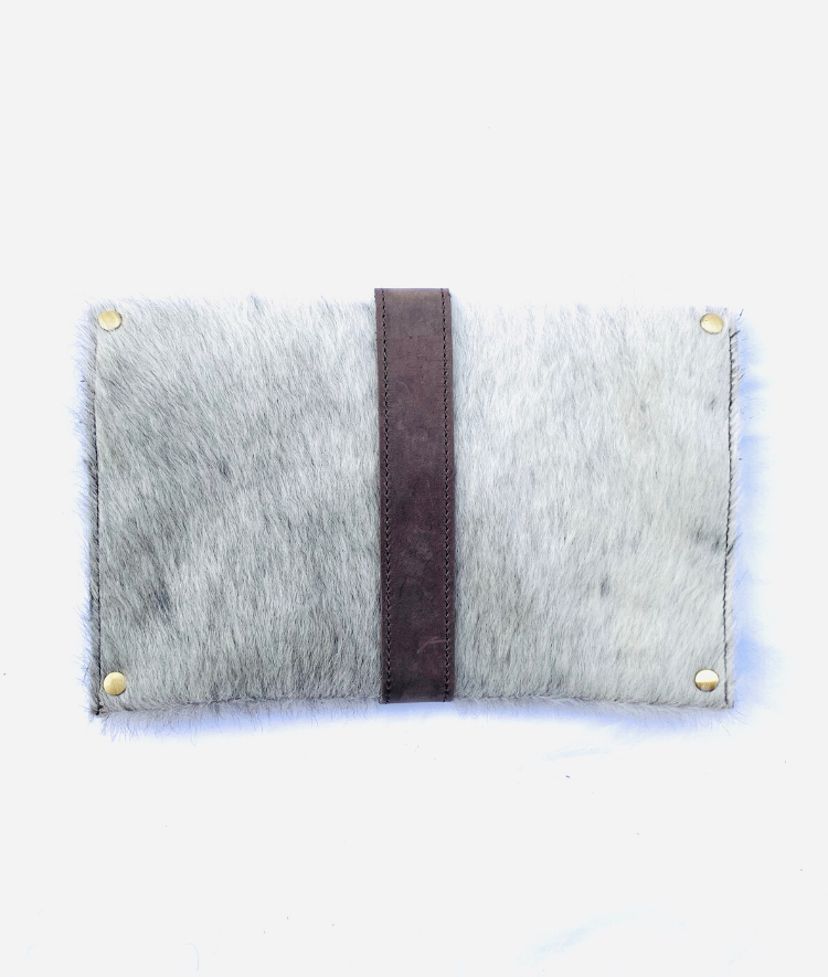 Back of artisan made cowhide clutch with grey hide and brown finished leather accents