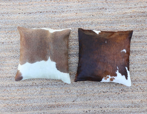 Two brown and white cowhide accent pillows displayed side by side
