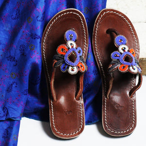 A pair of multicolored sandals that create meaningful work against a blue cloth