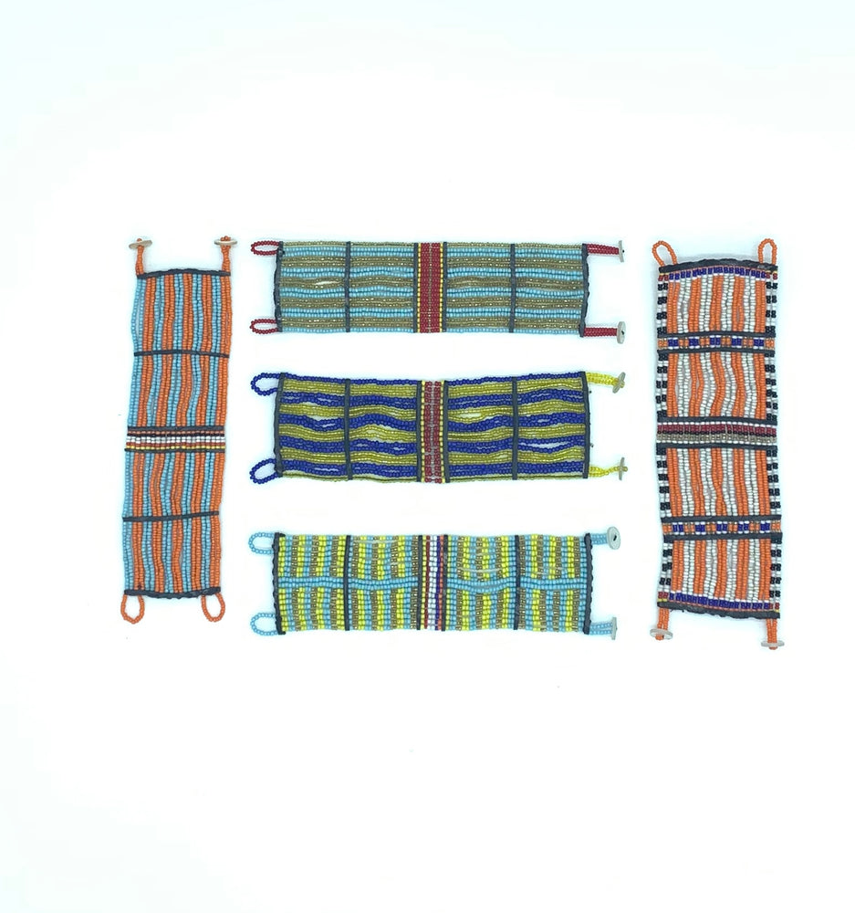 Several Kenyan beaded cuffs laid flat on a white background