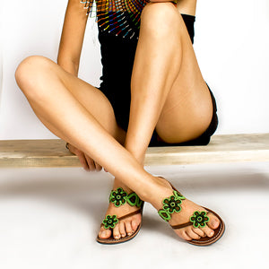A pair of green Kenyan beaded leather sandals with flower accents, the Maua sandal, on a model