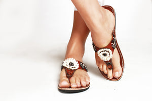 A pair of ethical beaded leather Kenyan sandals on a model with beading and seashells, the Malkia sandal