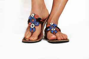 A pair of multicolored bohemian beaded sandals on a model against a white background