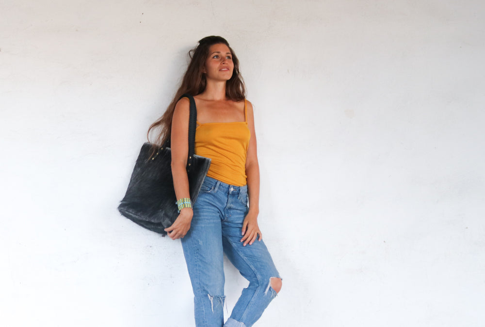 A model holding a grey cowhide tote bag handmade by artisans in Kenya