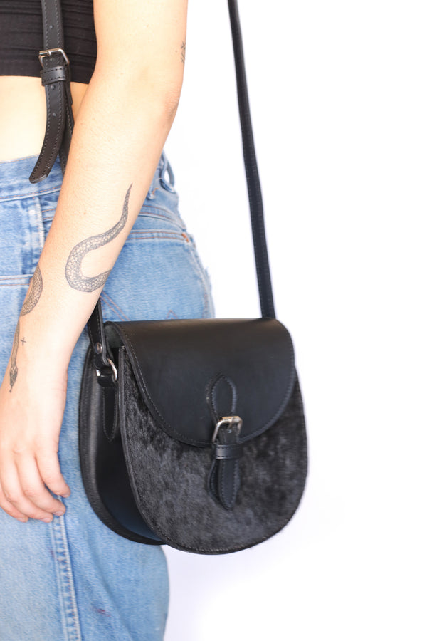 An artisan made Kenyan cowhide crossbody saddle purse in black hide and black finished leather on a model