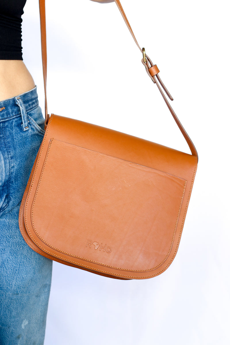 The back of a handmade cowhide crossbody saddle purse in tan and white hide and tan finished leather being worn by a model