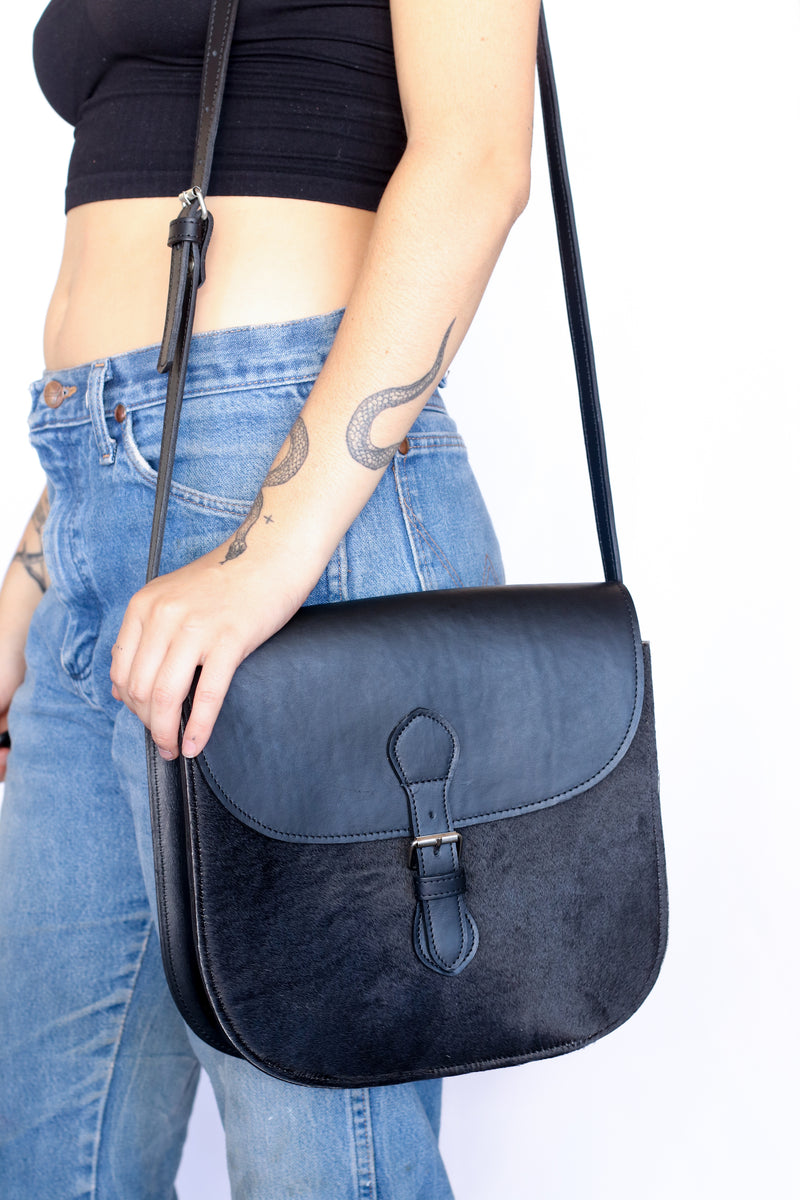 An artisan made crossbody purse in black hide and finished leather worn by a model