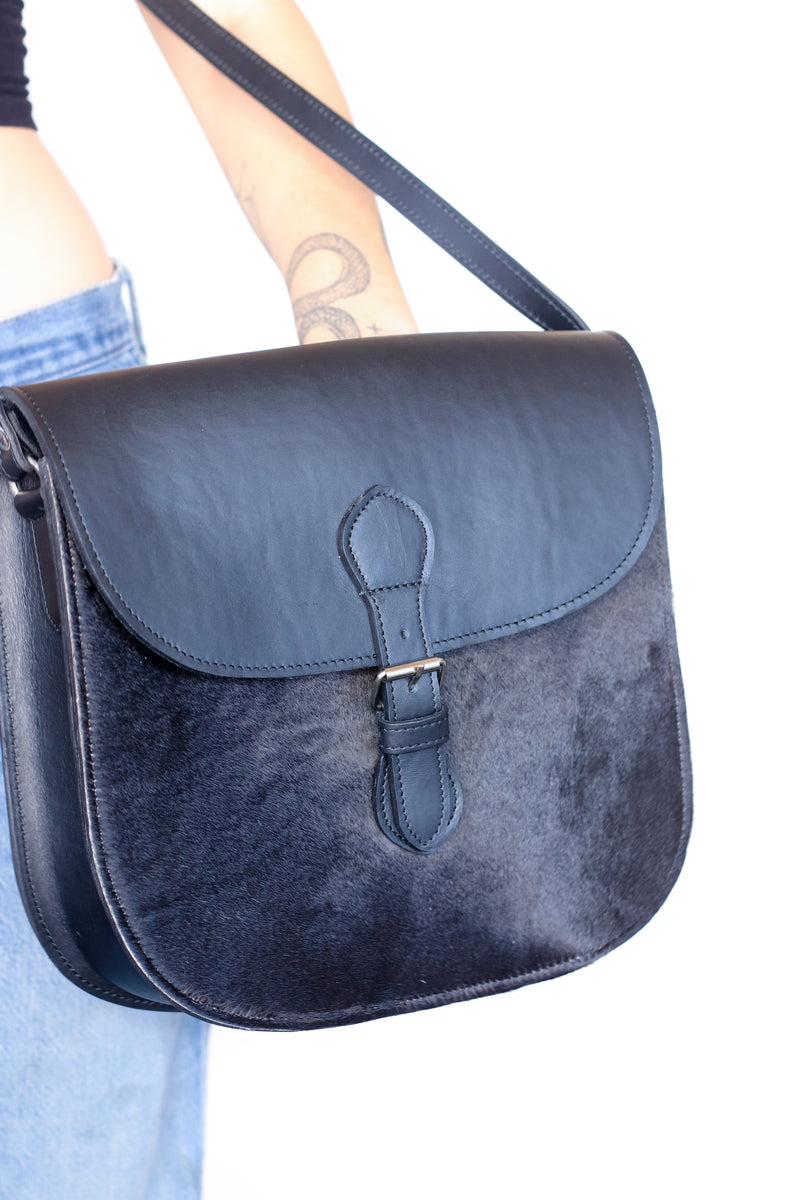 A handmade crossbody saddle purse in black hide and finished leather being held against a white back ground by a model
