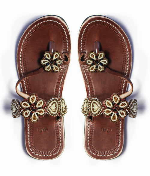 A pair of gold Kenyan beaded leather sandals with flower accents, the Maua sandal, on a white background