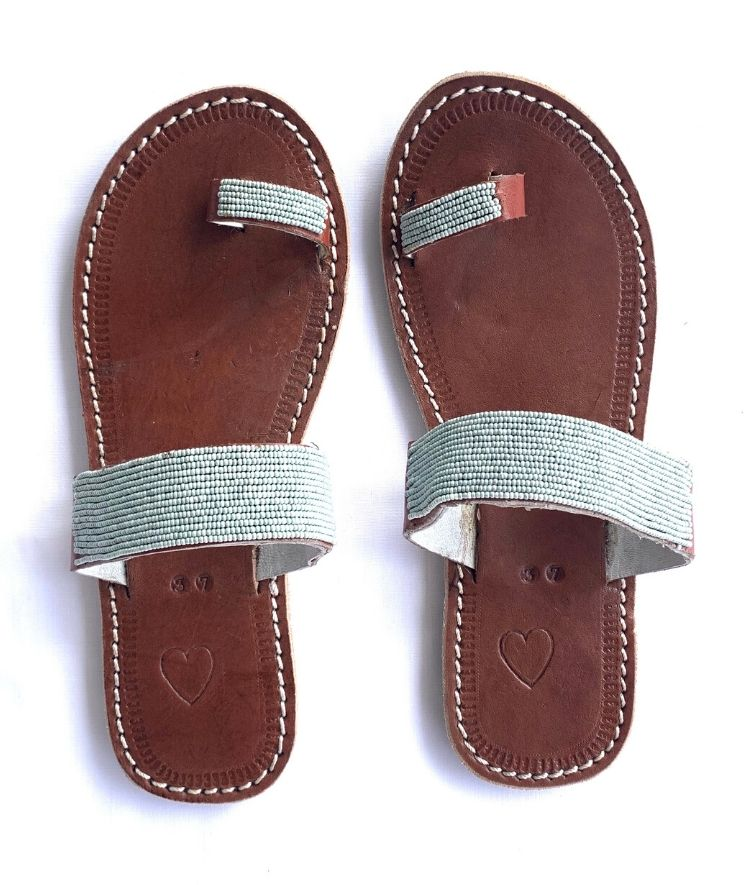 A pair of meaningful grey blue Kenyan beaded leather sandals, the Mkali sandal, on a white background