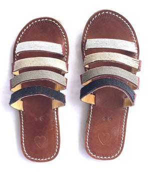 A pair of beaded leather Kenyan sandals on a white background with four straps
